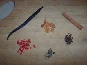 Clockwise from top left: vanilla bean, mace husk, cinnamon stick, cardamom seeds, black peppercorns, red peppercorns.