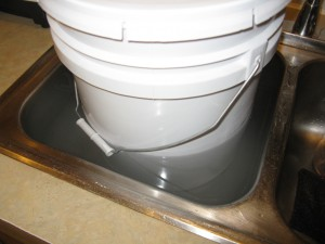 A 5 gallon bucket of crystallized/solidified honey, resting inside a sinkfull of hot water to help liquefy the honey.